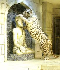 This white tiger examines his new playmate--a hand-carved statue of a monk