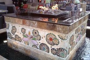 The fire and water feature at The Grotto in Houston features art glass mosaic sides and a fountain pool to delight guests while they dine.